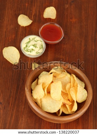 Potato chips  in wooden bowl and sauces, on wooden background - stock photo