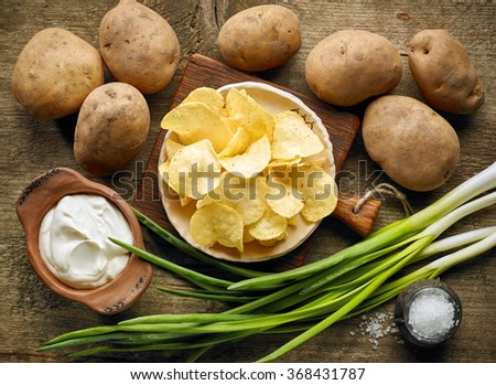 Potato chips ingredients on wooden table, top view - stock photo