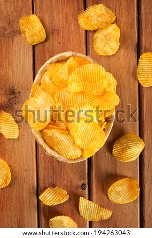 Potato chips on a wooden table. - stock photo