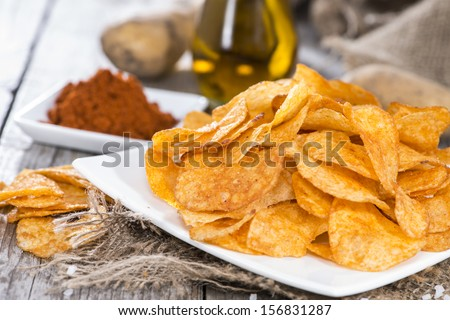 Potato Chips with portion of sunfloweroil and paprika powder - stock photo
