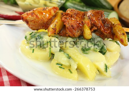 Potato-cucumber salad with fiery fire skewers and parsley - stock photo