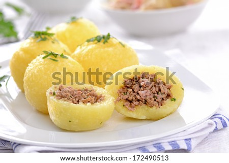Potato dumplings stuffed with minced meat and served with sauerkraut and bacon - stock photo