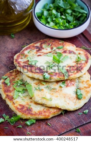 Potato flatbread with herbs, rustic vegetable dish, delicious summer snack - stock photo
