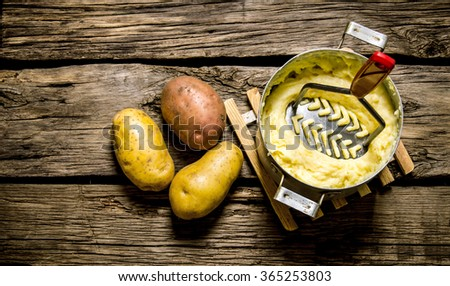 Potato food . Cooking mashed potatoes with pestle on wooden background. Top view - stock photo