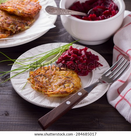 Potato fritters, beet salad, a bunch of green onions on a wooden surface - stock photo