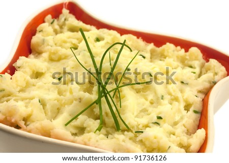 Potato mash with chives in a orange retro bowl - stock photo