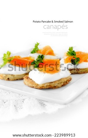 Potato Pancake and Smoked Salmon Canapes against a white background.  - stock photo