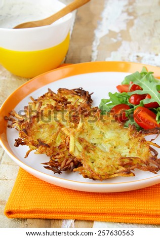 potato pancakes served with salad and sour cream - stock photo