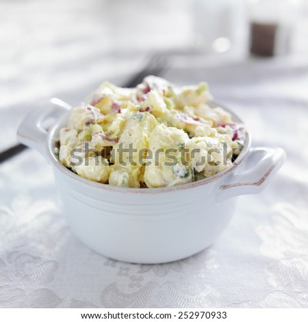 potato salad shot with selective focus in stoneware - stock photo