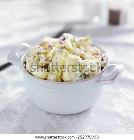potato salad shot with selective focus in stoneware - stock photo