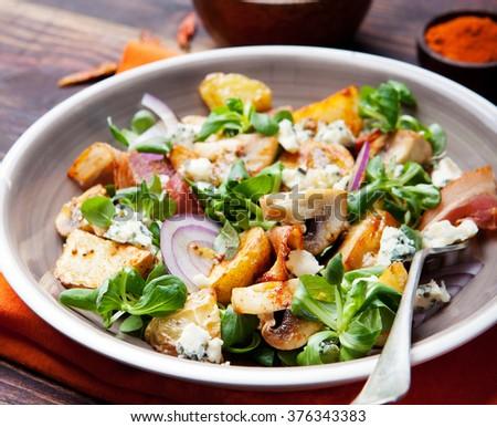 Potato salad with bacon, mushroom on orange napkin Wooden background - stock photo