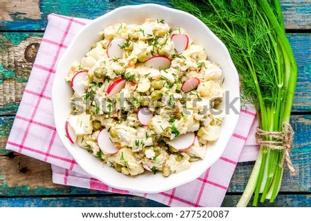 potato salad with fresh radishes in a white bowl  with dill and green onion on a rustic wooden table - stock photo