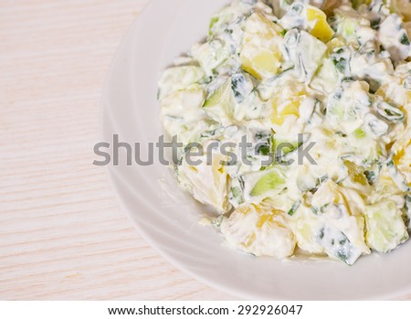 Potato salad with green onions and cucumber - stock photo