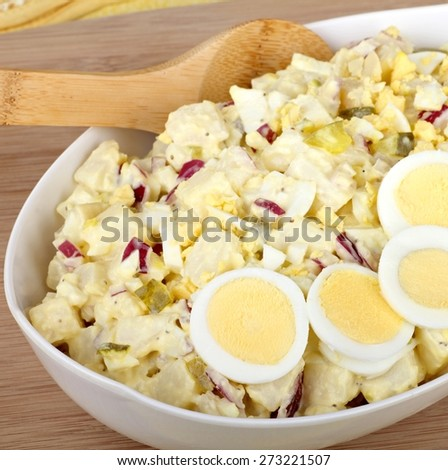 Potato salad with sliced eggs in a serving bowl - stock photo