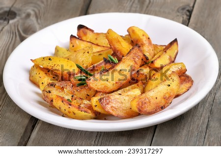 Potato wedges on white plate, fast food, close up view - stock photo