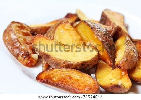 Potato wedges roasted in their skins. Golden and crispy - stock photo