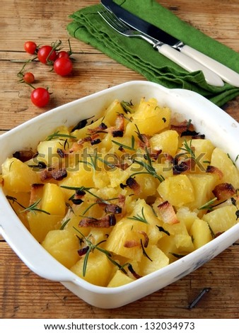 Potatoes baked with bacon and rosemary - stock photo