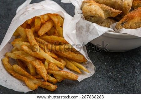 Potatoes fries in a little white paper bag on a black background - stock photo