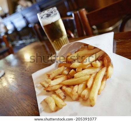 Potatoes fries in a little white paper bag on wood table in brussels pub - stock photo