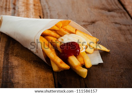 Potatoes fries in a little white paper bag with ketchup and mayonnais on wood board - stock photo