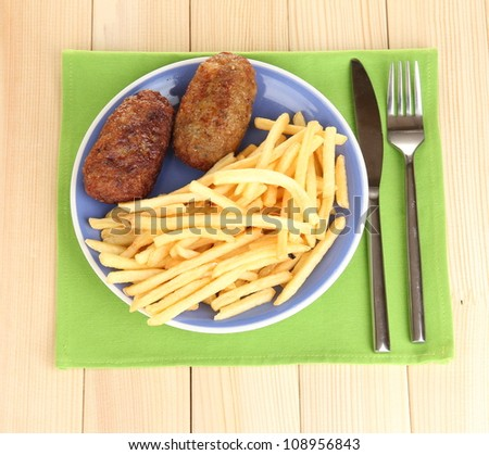 Potatoes fries with burgers on the plate on wooden background close-up - stock photo