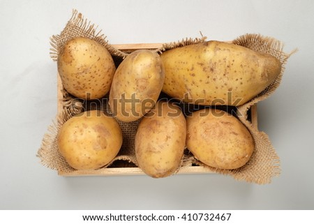Potatoes in the Wooden Crate on white background, top view - stock photo