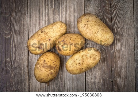Potatoes on wooden background. Top view. - stock photo