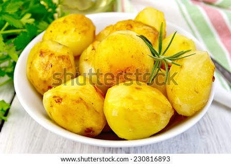 Potatoes roasted with rosemary in a white plate, napkin, parsley, oil, fork on the background of bright wooden planks - stock photo
