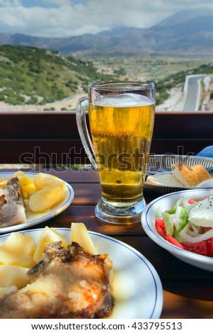 Potatoes with a piece of pork, Greek salad and glass of beer. Verandah Cafe on the pass with a view of the plateau of Lassithi. Crete - stock photo