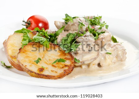 potatoes with mushrooms tomato sauce on a plate - stock photo