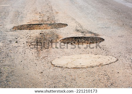 Pothole in pavement signifying failing infrastructure - stock photo