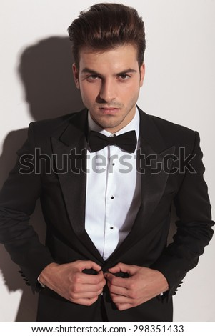 Potrait of a attractive business man looking at the camera while unbutonning his jacket. - stock photo