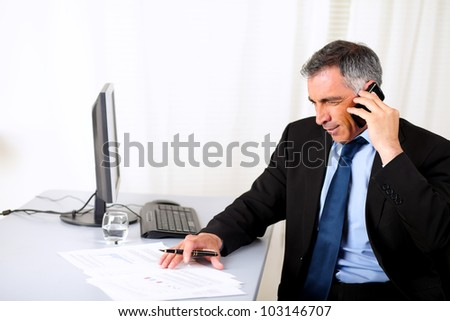 Potrait of a attractive businessman speaking on mobile at the office - stock photo
