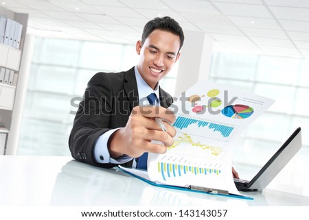 potrait of successful businessman showing growth chart and smiling - stock photo