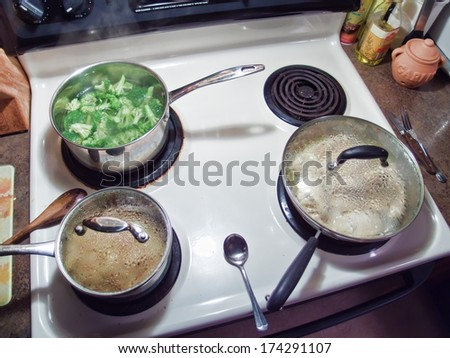 Pots and Pans cooking on stove - stock photo