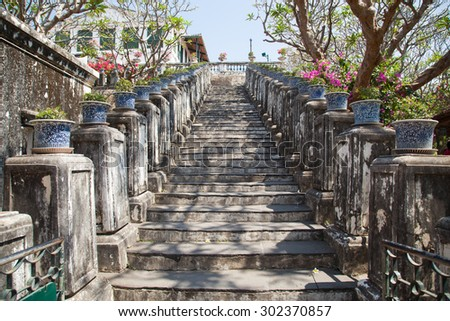 Potted plants on a railing in a park along the sidewalks. - stock photo