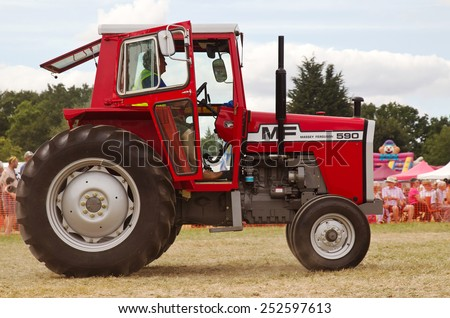 POTTEN END, UK - JULY 27: A Massey Ferguson vintage tractor is shown around the main arena as part of the agricultural machinery show at the Dacorum Steam & Country fair on July 27, 2014 in Potten End - stock photo