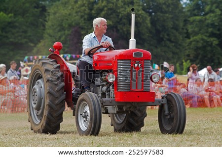POTTEN END, UK - JULY 27: A veteran Massey Ferguson tractor is shown around the main arena as part of the agricultural machinery show at the Dacorum Steam & Country fair on July 27, 2014 in Potten End - stock photo