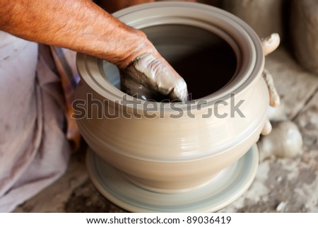 potter giving shape to his vase on the wheal - stock photo