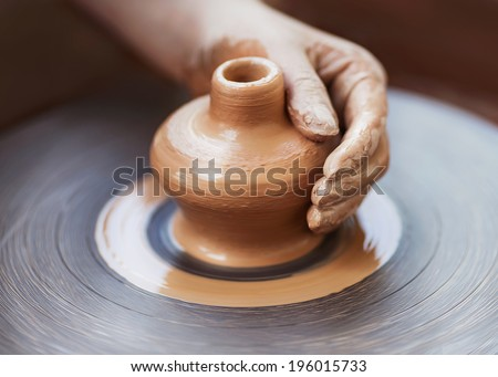 Potter hands making in clay on pottery wheel. Potter makes on the pottery wheel clay pot. - stock photo