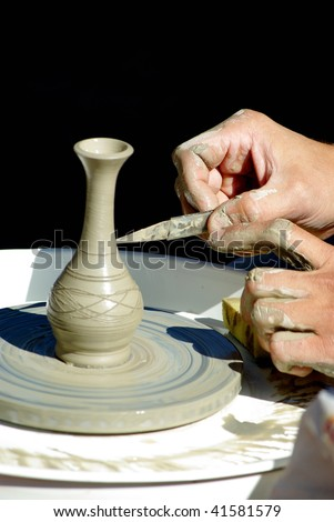 Potter's hands at work on decorating crude clay pot on the jigger - stock photo