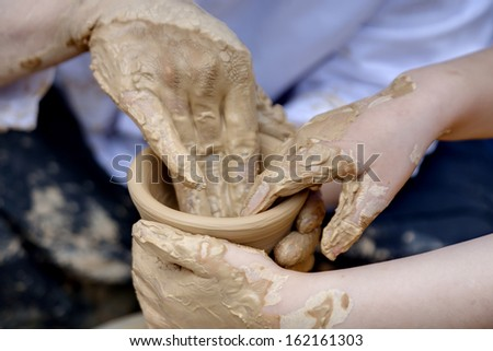 Potters hands helping a child hands to do a pottery - stock photo