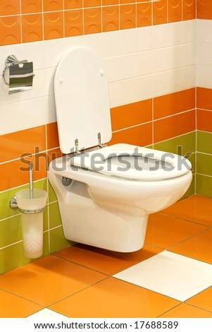 Potty seat in vivid orange and green toilet - stock photo