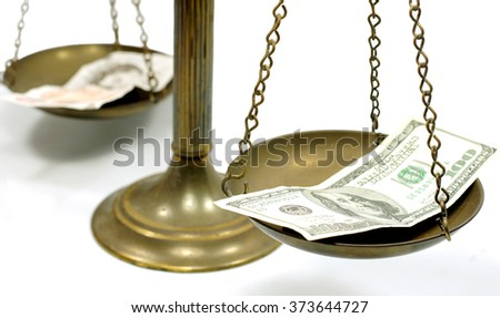 Pound and dollar notes on scale in a conceptual photo - stock photo
