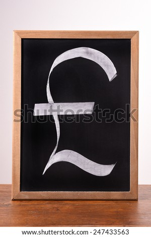 pound sterling sign written with a chalk on a blackboard    - stock photo