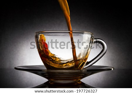 Pour coffee into transparent glass cup on dark background. - stock photo