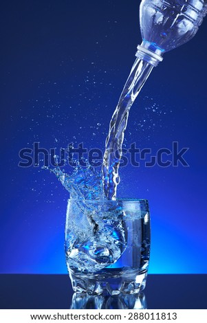 Pour fresh splash water on glass, blue background. Pitcher of water poured into a glass. Image refreshing water that is poured and produces splashes and drops of water. Cool healthy purity beverage. - stock photo