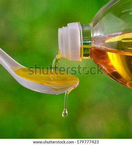 Pour peanut oil into a spoon. - stock photo