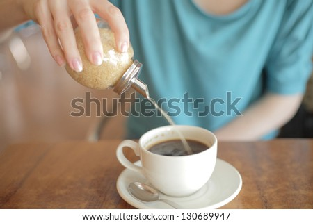 pour sugar to the hot aromatic coffee - stock photo