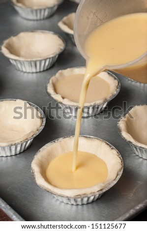 Pour the egg custard mixture into each tart shell. - stock photo